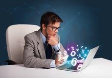 Gut aussehender Mann, der am Schreibtisch sitzt und auf Laptop mit Zahl 3d schreibt Lizenzfreies Stockbild