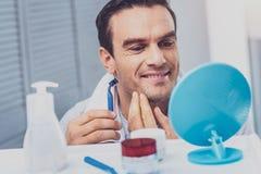 Gut aussehender Mann, der sein Gesicht untersucht den Spiegel rasiert lizenzfreie stockbilder