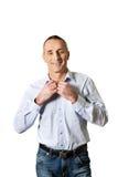 Gut aussehender Mann, der sein Hemd knöpft Lizenzfreie Stockfotografie