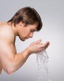 Gut aussehender Mann, der sein sauberes Gesicht wäscht Stockbilder