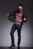 Gut aussehender Mann, der seine schwarze Lederjacke zieht Lizenzfreie Stockbilder