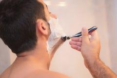Gut aussehender Mann, der seinen Bart im Badezimmer rasiert lizenzfreie stockfotos