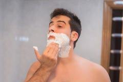 Gut aussehender Mann, der seinen Bart im Badezimmer rasiert stockbilder