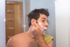 Gut aussehender Mann, der seinen Bart im Badezimmer rasiert lizenzfreie stockbilder