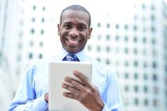 Gut aussehender Mann, der seinen Tablet-Computer verwendet Lizenzfreie Stockbilder