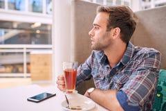 Gut aussehender Mann, der seitlich beim Halten seines Tees im Café schaut Stockfoto