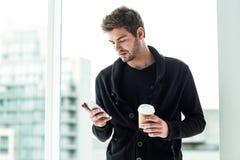 Gut aussehender Mann, der Smartphone verwendet und Wegwerfschale hält Lizenzfreies Stockfoto