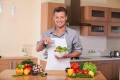 Gut aussehender Mann, der solt frischem Salat hinzufügt Stockfotos