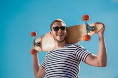 Gut aussehender Mann in der Sonnenbrille, die Skateboard, blauen Himmel auf Hintergrund hält Stockfoto
