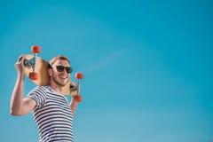 Gut aussehender Mann in der Sonnenbrille, die Skateboard, blauen Himmel auf Hintergrund hält Stockfotos