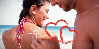 Gut aussehender Mann, der Sonnenschutzmittel auf seine Freundin setzt Stockbilder