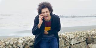 Gut aussehender Mann, der am Telefon vor dem Ozean lacht Stockfotografie