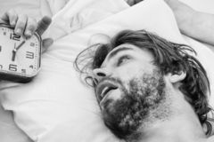 Gut aussehender Mann, der Uhr im Bett verwendet, nachdem morgens aufwachen Glückliches in den steigenden Händen des Betts herein  lizenzfreie stockfotografie