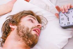Gut aussehender Mann, der Uhr im Bett verwendet, nachdem morgens aufwachen Gl?ckliches in den steigenden H?nden des Betts herein  stockfotos