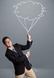 Gut aussehender Mann, der Wolkenballonzeichnung hält Stockfotos