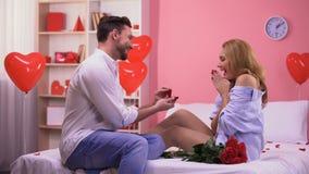 Gut aussehender Mann, der zu überraschter Freundin, Ring und Bündel Rosen gebend vorschlägt stock footage