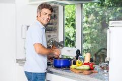 Gut aussehender Mann, der zu Hause Küchenlächeln kocht Stockfotos