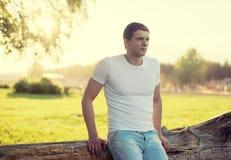 Gut aussehender Mann draußen, weicher sonniger Sonnenuntergang, bemannen nachdenkliches Stockbild
