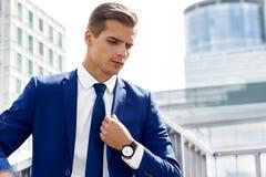 Gut aussehender Mann in einer blauen Klage gegen einen Stadthintergrund an einem sonnigen Tag Lizenzfreie Stockbilder