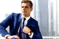 Gut aussehender Mann in einer blauen Klage gegen einen Stadthintergrund an einem sonnigen Tag Stockfoto