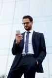 Gut aussehender Mann in einer stilvollen Klage mit dem Telefon ist nahe einem Bürohohen gebäude Lizenzfreies Stockbild