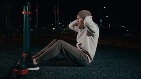 Gut aussehender Mann führt Torsoaufzüge im Nachttraining im Park durch stock footage