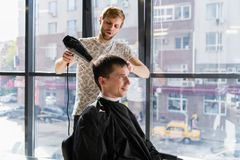 Gut aussehender Mann am Friseur-Blow Drying His-Haar stockfoto