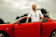 Gut aussehender Mann geht roten Sportwagen hinaus Stockfotografie