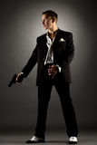 Gut aussehender Mann gekleidet als Gangster, der Gewehr hält Lizenzfreies Stockfoto