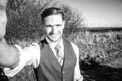 Gut aussehender Mann gekleidet in einer Klage, die selfie mit Landschaft und Bäume im Hintergrund nimmt stockfotografie