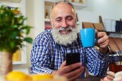 Gut aussehender Mann im überprüften Hemd, das in der Küche und im Halten sitzt lizenzfreie stockfotografie