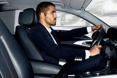 Gut aussehender Mann im Auto Portrait des Geschäftsmannes mit Glas des Weinbrands und der Zigarre Lizenzfreie Stockfotografie