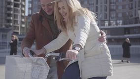 Gut aussehender Mann im braunen Mantel seine Freundin unterrichtend, Fahrrad in der Stadt zu fahren Freizeit von schönen Paaren d stock footage