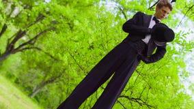 Gut aussehender Mann im Kostüm geht auf Stelzen am Park nahe Baum stock video
