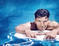 Gut aussehender Mann im Pool Stockbild