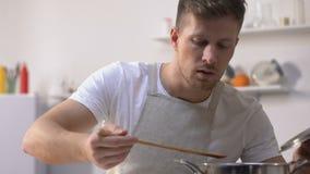 Gut aussehender Mann im Schutzblech kochend, Bestandteile in der Wanne rührend und Mahlzeit versuchend stock footage