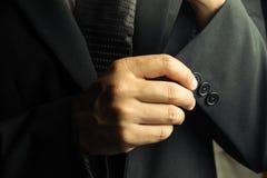 Gut aussehender Mann im schwarzen Anzug auf einem schwarzen Hintergrund Lizenzfreie Stockbilder