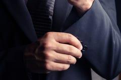 Gut aussehender Mann im schwarzen Anzug auf einem schwarzen Hintergrund Lizenzfreie Stockfotos