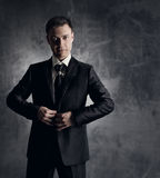 Gut aussehender Mann im schwarzen Anzug. Wedding Bräutigammode. Graues backgrou Stockfotos