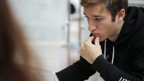 Gut aussehender Mann im schwarzen Hoodie arbeitet an dem Laptop, der im Büro sitzt stock video