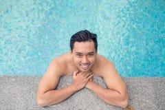 Gut aussehender Mann im Swimmingpool Stockbild