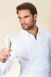 Gut aussehender Mann im weißen Hemd feiernd mit einem Glas Champagner lizenzfreie stockfotografie