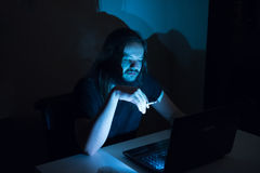 Gut aussehender Mann ist Faltenbesatzzigaretten vor seinem Computer Lizenzfreies Stockfoto