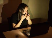 Gut aussehender Mann ist Faltenbesatzzigaretten vor seinem Computer Lizenzfreie Stockfotografie