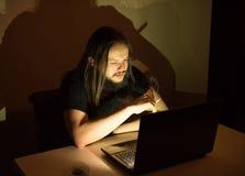 Gut aussehender Mann ist Faltenbesatzzigaretten vor seinem Computer Stockfotos