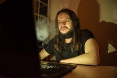 Gut aussehender Mann ist Faltenbesatzzigaretten vor seinem Computer Stockfotografie