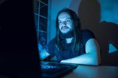 Gut aussehender Mann ist Faltenbesatzzigaretten vor seinem Computer Stockbilder