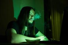 Gut aussehender Mann ist Faltenbesatzzigaretten vor seinem Computer Stockbild