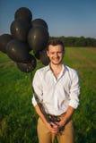 Gut aussehender Mann mit Ballonen auf dem Gebiet Lizenzfreie Stockfotos