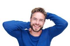 Gut aussehender Mann mit Bart lachend mit den Händen im Haar Stockfoto
